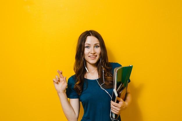 Linda garota segurando livros e ouvindo música nos fones de ouvido