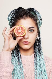 Linda garota segurando metade de uma laranja vermelha