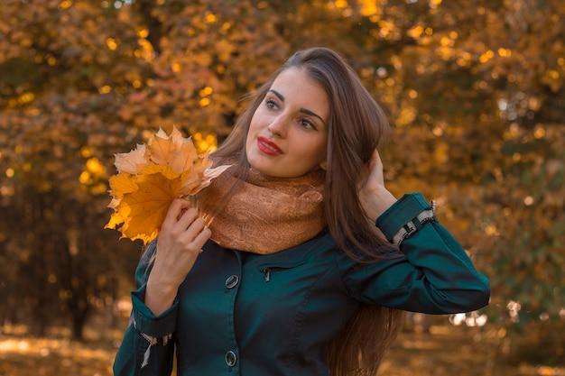 Linda garota segurando o cabelo com uma mão enquanto a outra segura as folhas, close-up