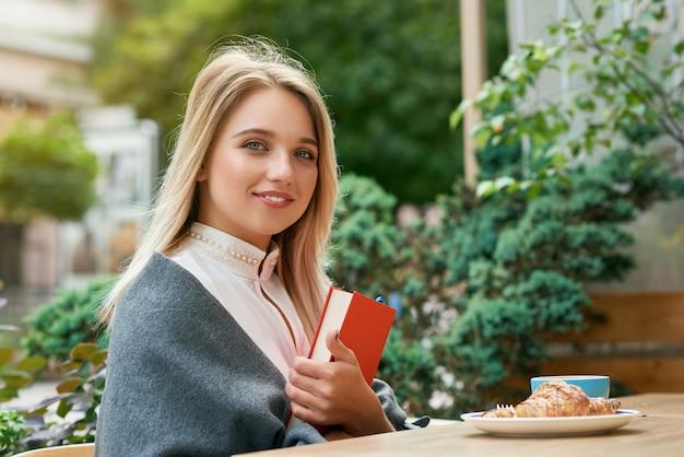 Linda garota segurando o livro vermelho grande, sentado ao ar livre café, comendo croissant.