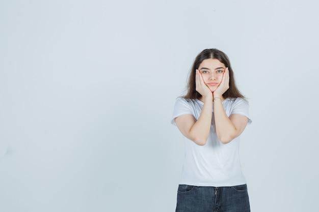 Linda garota segurando o rosto com as mãos na camiseta, jeans e olhando sério. vista frontal.