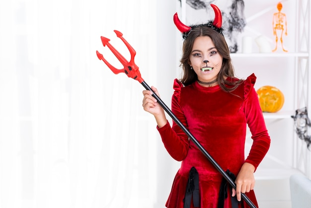 Linda garota segurando o tridente de halloween