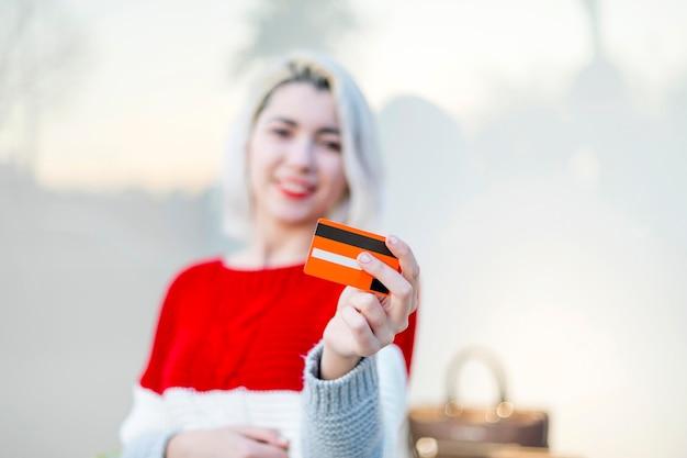 Linda garota segurando um cartão de crédito