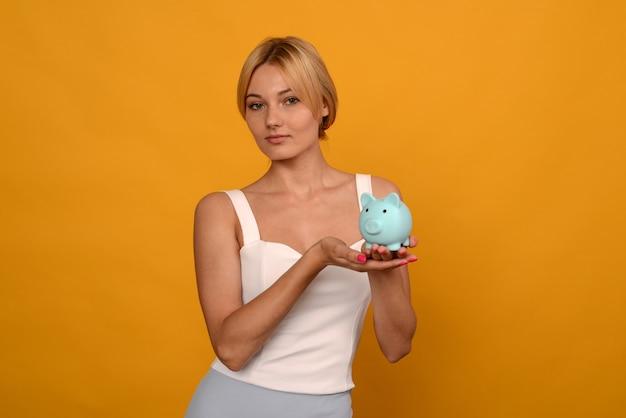 Linda garota segurando um cofrinho de porco em fundo amarelo. para economizar dinheiro e conceito financeiro.