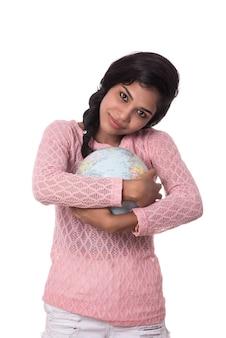 Linda garota segurando um globo do mundo isolado em um espaço em branco