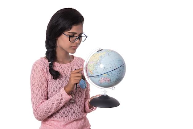 Linda garota segurando um globo terrestre isolado