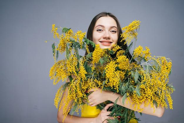 Linda garota segurando um grande buquê de mimosa perfumada amarela, feliz primavera e calor