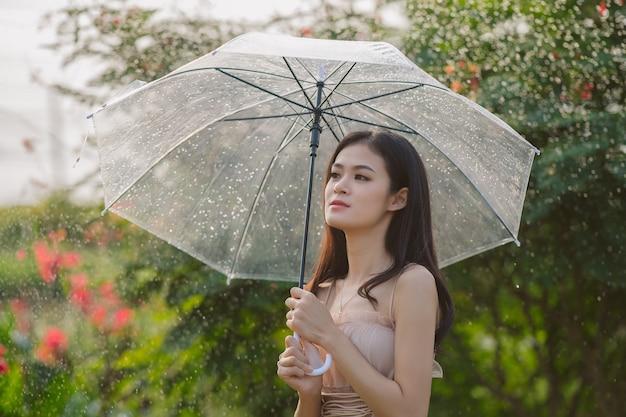 Linda garota segurando um guarda-chuva enquanto caminha no parque