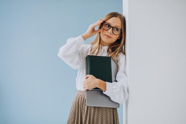 Linda garota segurando um livro e um laptop no escritório