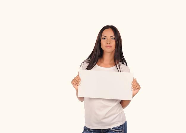 Linda garota segurando um outdoor em branco isolado no fundo branco
