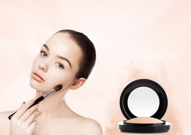 Linda garota segurando um pincel de maquiagem como base