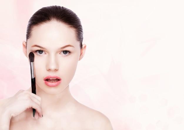 Linda garota segurando um pincel de maquiagem para base de pó no fundo rosa bokeh
