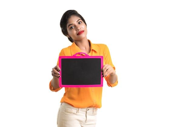 Linda garota segurando um quadro-negro ou ardósia, isolada sobre fundo branco