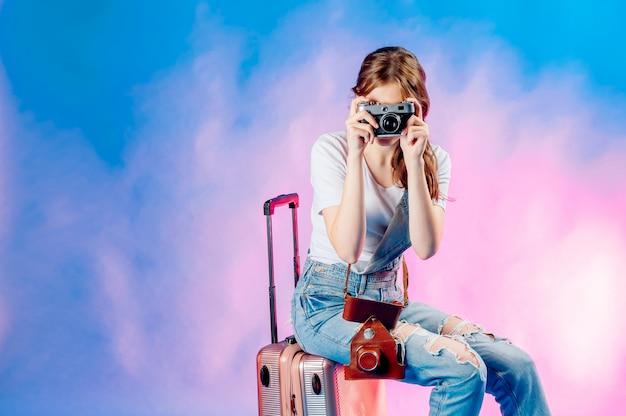 Linda garota segurando uma câmera com uma mala em um fundo azul vai viajar