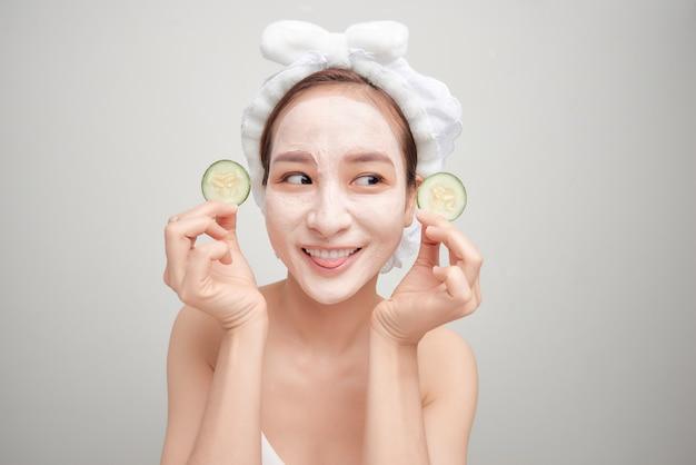 Linda garota segurando uma fatia de pepino na frente do rosto com máscara de argila.
