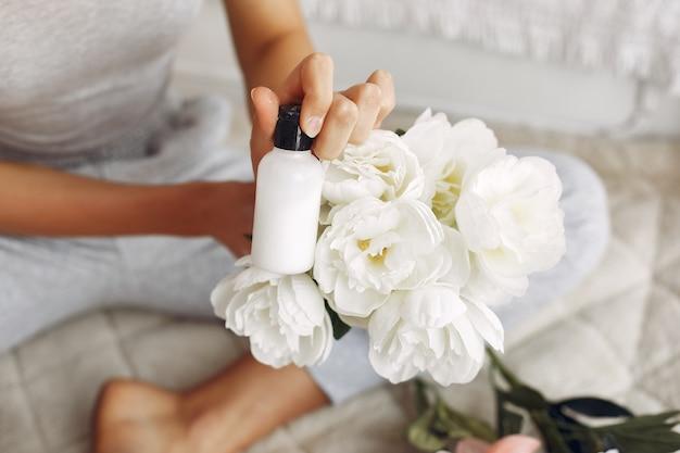 Linda garota segurando uma garrafa de creme e buquê de flores
