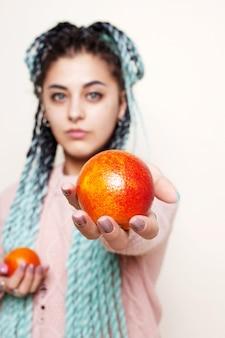 Linda garota segurando uma laranja vermelha
