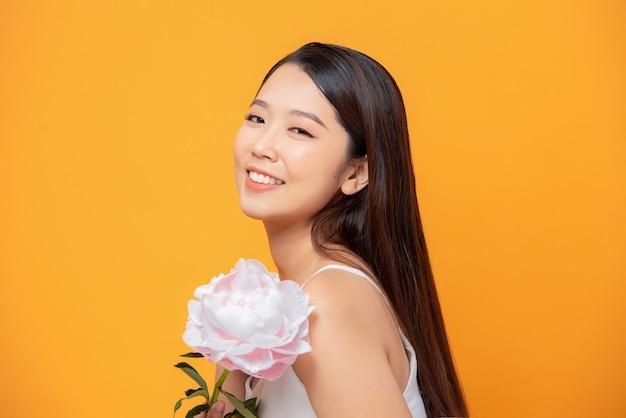 Linda garota sensual com cabelo comprido e flores de uma peônia rosa.