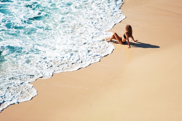 Linda garota senta-se em uma praia selvagem. vista incrível do topo.