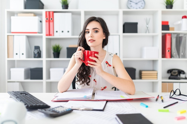 Linda garota senta-se na mesa de escritório e detém uma caneca vermelha nas mãos.