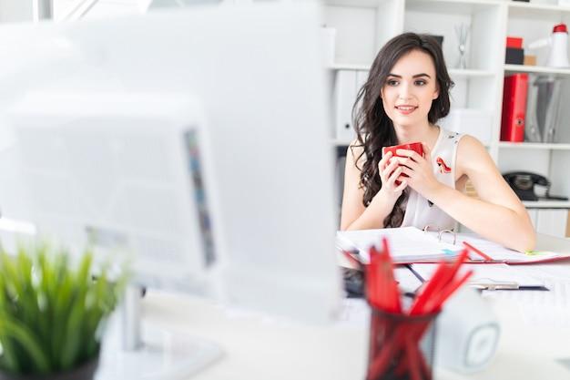 Linda garota senta-se na mesa de escritório, olha para a tela do computador e tem uma caneca vermelha nas mãos.