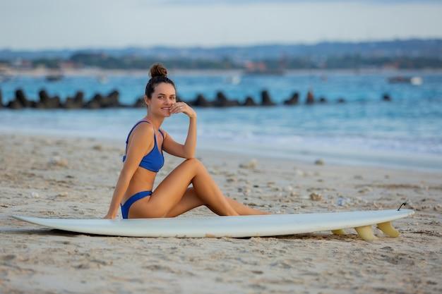 Linda garota senta-se na praia com uma prancha de surf.
