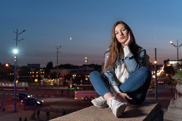 Linda garota senta-se no fundo da cidade à noite. aluna elegante solitária sentada no degrau mais alto.