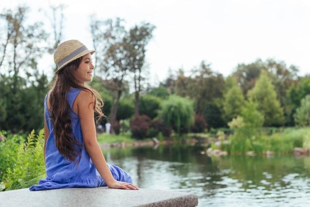 Linda garota sentada à beira do lago por trás