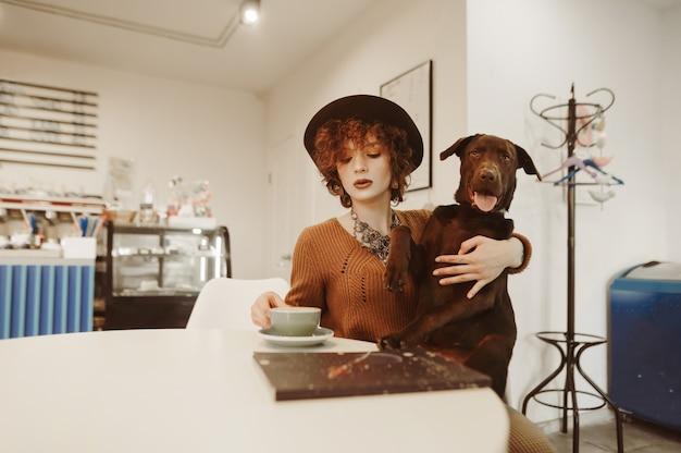 Linda garota sentada à mesa com um cachorro em um aconchegante café leve e bebendo café