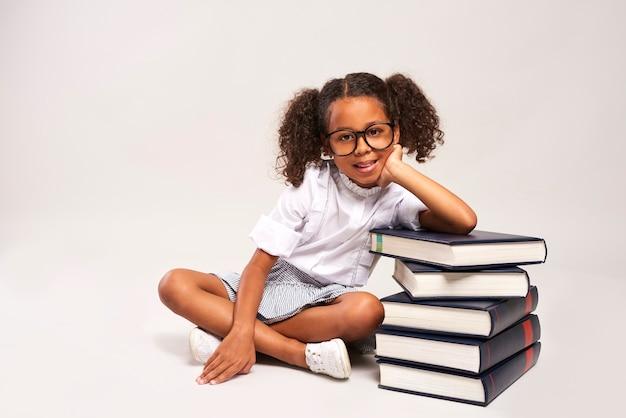 Linda garota sentada ao lado de uma pilha de livros