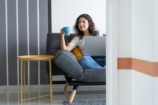 Linda garota sentada com um laptop em um sofá em uma sala elegante. trabalho a partir de casa. ambiente de trabalho de bom humor