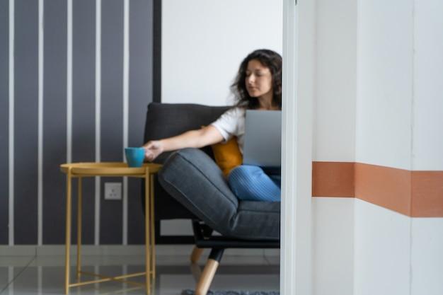 Linda garota sentada com um laptop no sofá em uma sala elegante. trabalho a partir de casa. ambiente de trabalho de bom humor