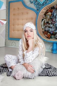 Linda garota sentada em pijama pela manhã. máscara do sono.
