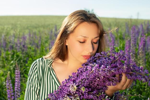 Linda garota sentada em um campo florido fechou os olhos e cheirou a flores de tremoço