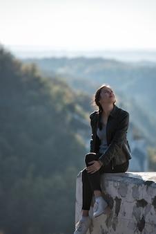 Linda garota sentada em um penhasco no fundo da natureza e olhando para o céu. quadro vertical.