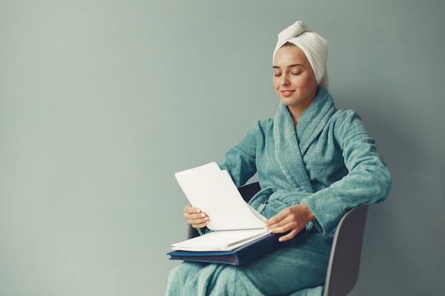 Linda garota sentada em um roupão azul