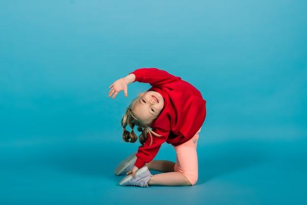 Linda garota sentada em uma divisão isolada em um fundo azul