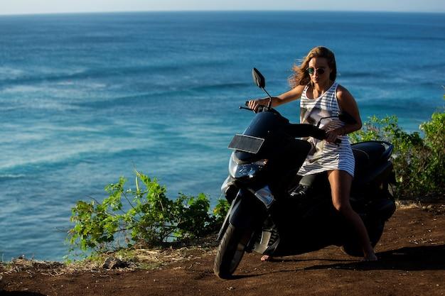 Linda garota sentada em uma scooter em um penhasco com uma vista incrível para o mar.