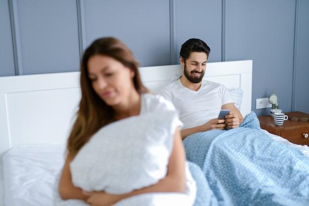 Linda garota sentada na cama e parecendo triste, enquanto os namorados dela não prestam atenção nela. ele está sorrindo e olhando para o telefone.