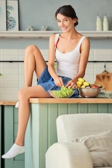 Linda garota sentada na cozinha na mesa com frutas frescas