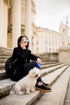 Linda garota sentada na escada com seu cachorro de estimação depois de um passeio em viena, áustria