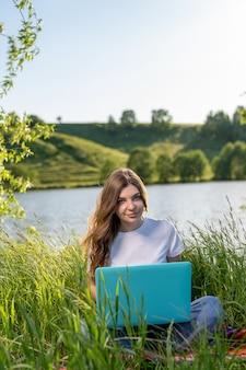 Linda garota sentada na grama verde à beira do lago com laptops no colo