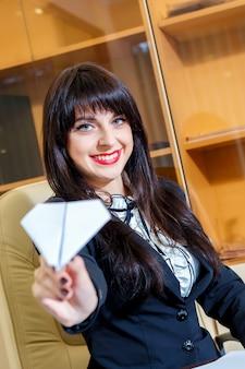 Linda garota sentada na mesa do escritório e lança um avião de papel