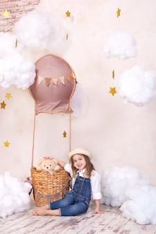 Linda garota sentada na parede de um balão, estrelas e nuvens e segurando um ursinho de pelúcia. menina está sonhando. menina brinca no quarto das crianças com um brinquedo. decoração de quarto de criança. bebê e brinquedos de pelúcia