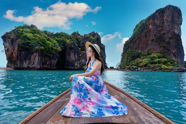 Linda garota sentada no barco na ilha de james bond em phang nga, tailândia.