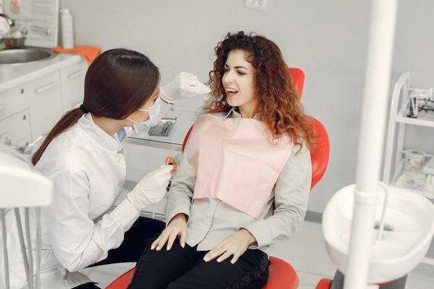 Linda garota sentada no consultório do dentista