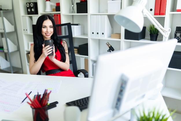 Linda garota sentada no escritório na mesa e segurando um copo de café