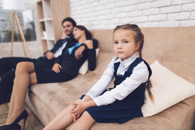 Linda garota sentada no sofá ao lado dos pais.