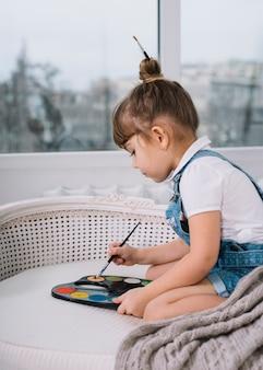 Linda garota sentada no sofá com paleta brilhante aquarelle