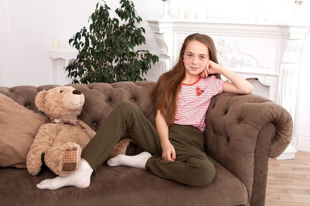 Linda garota sentada no sofá, sorrindo e olhando
